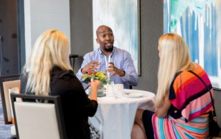 Man sitting at a table at a conference networking with two women