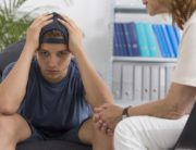 Depressed young man with counselor