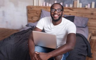 joyful man with laptop in aparment